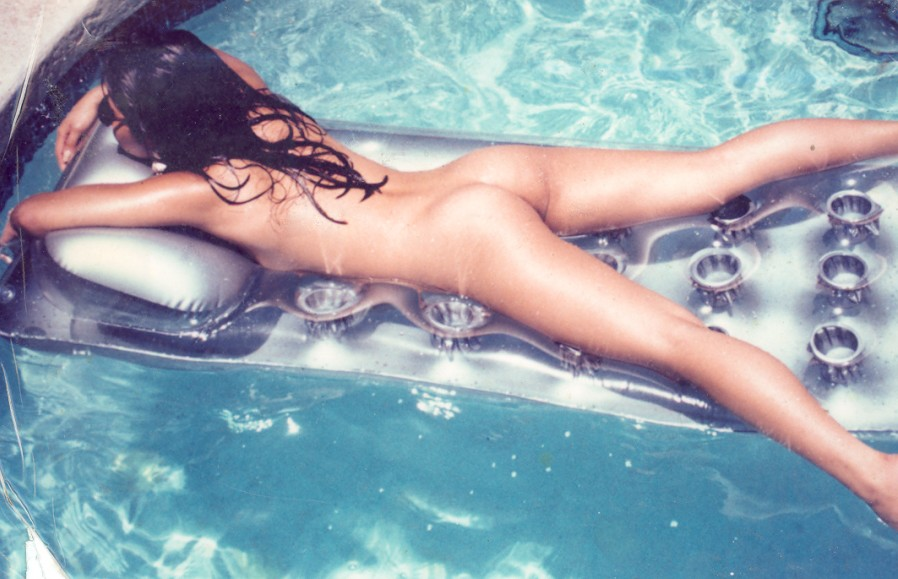 Beautiful naked girl floating in pool